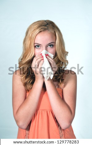 Teenage girl Sneezing into a tissue