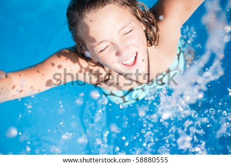 Teenage girl splashing water up toward the camera in a pool.