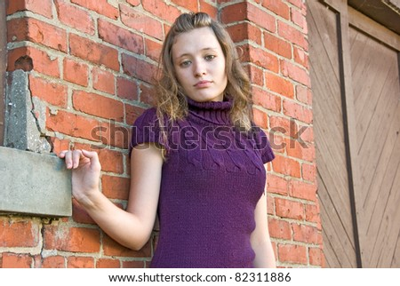 teenage girl standing by old brick wall