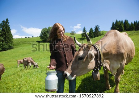 Teenage girl standing in pasture with cows