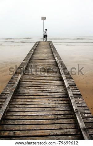 teenage girl standing on old sea pier, Italy - stock photo