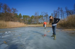 teenage girl stands on the ice of the lake