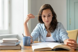 Teenage girl studying reading book at home concentrating looking down