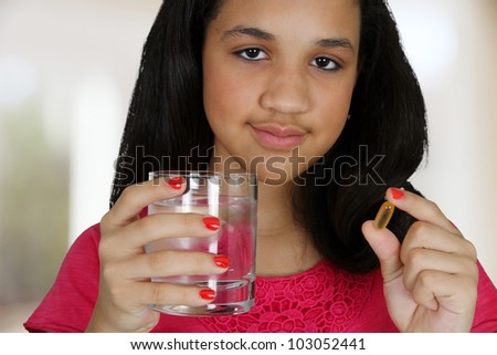 Teenage girl taking a pill at her home
