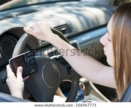 Teenage girl texting on cell phone while driving - stock photo