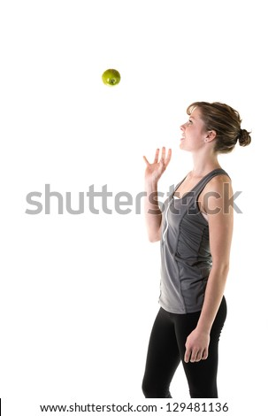 Teenage girl throwing an apple in the air. Isolated on white background