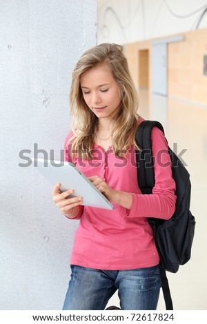 Teenage girl using electronic tablet at school