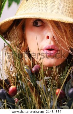 Teenage girl wearing safari hat hiding in the jungle