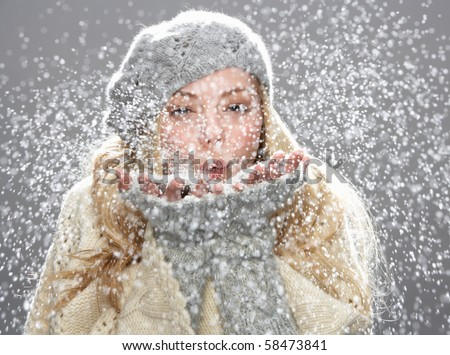 Teenage Girl Wearing Warm Winter Clothes And Hat Blowing Snow In Studio