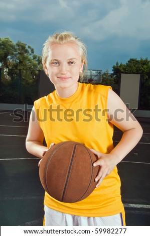 Teenage girl wearing yellow holding basketball at the street playground