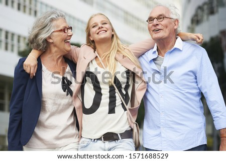 Teenage girl with arms around grandparents in city
