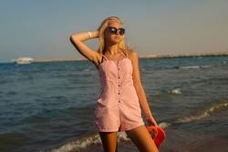 teenage girl with blonde hair on the beach.