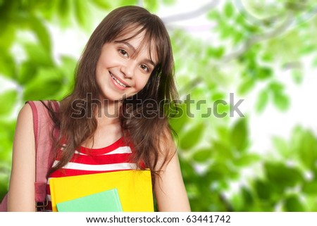 Teenage girl with books outside under green trees