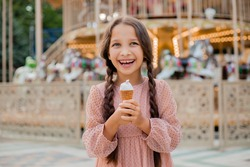 Teenage girl with dark hair and pigtails with ice cream at amusement park