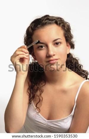 Teenage girl with eyebrow brush
