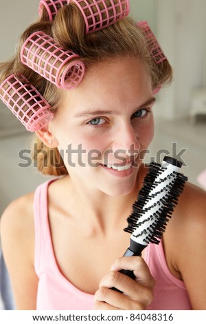 Teenage girl with hair in curlers