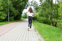 Teenage girl with long brown hair wearing black jeans with chain and sneakers walking away by pavement pathway in summerd day, green grass and trees on background, back view.