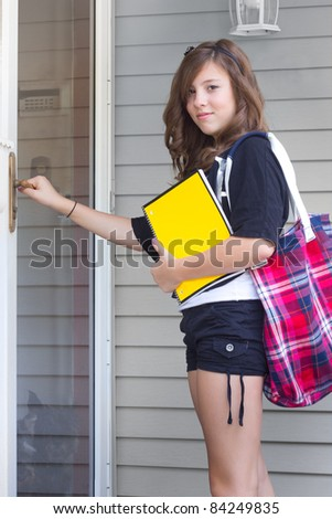 Teenage girl with notebook and book bag returning home from school