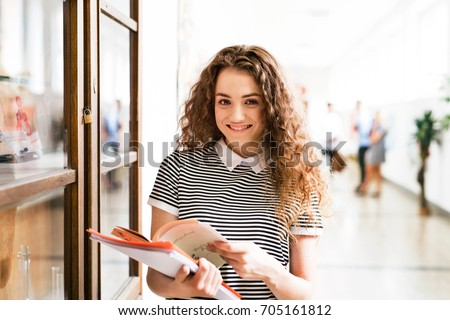 Teenage girl with notebooks in high school hall during break. Foto stock ©