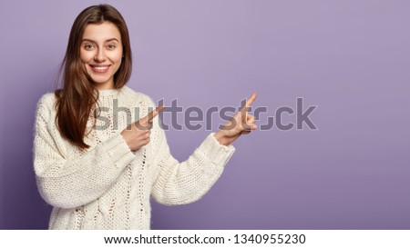 Photo of Teenage girl with smile on face, long dark hair, dressed in long sleeved jumper, promots object on right free space, isolated over purple background, shows direction to place of entertainment