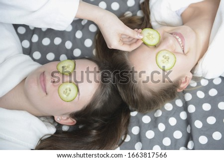 Teenage girlfriends with cucumber slices over eyes