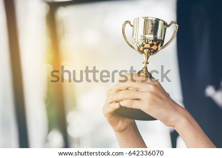 Teenage girls' hands are holding trophies, congratulations on success.Conception of victory in the competition.Focus on the trophy