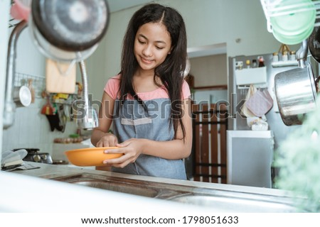 teenage girls happily do the household chores washing dishes doing activities during the pandemic at home Foto d'archivio ©