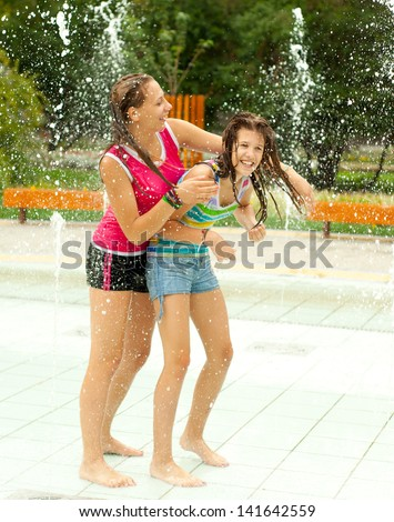 Teenage girls having fun in the towns water fountain on hot summer day.