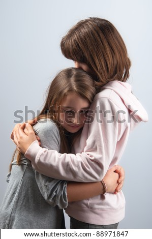 Teenage girls hugging each other in mutual support.