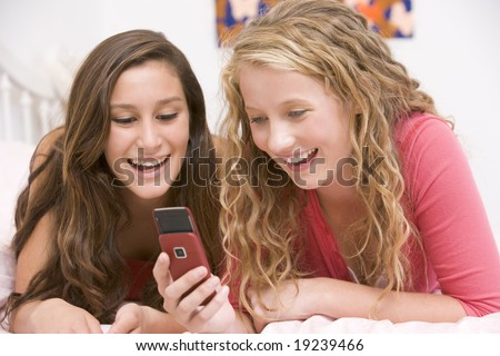 Teenage Girls Lying On Bed Texting