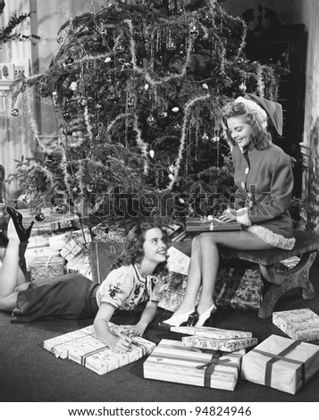 Teenage girls with presents and Christmas tree
