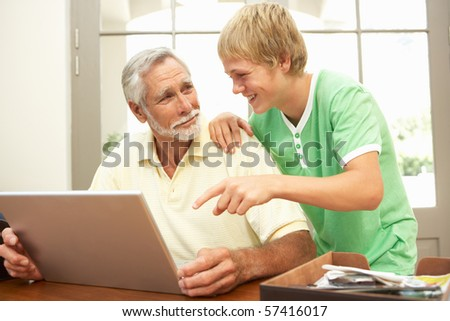 Teenage Grandson Helping Grandfather To Use Laptop At Home