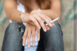 Teenage hands holding cigarette.