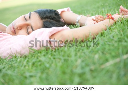 Teenage Indian girl sleeping while laying down on green grass in the park.