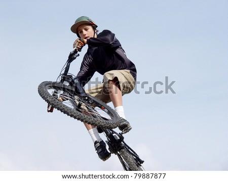 Teenage male doing high jump on a bmx bike, blue sky background
