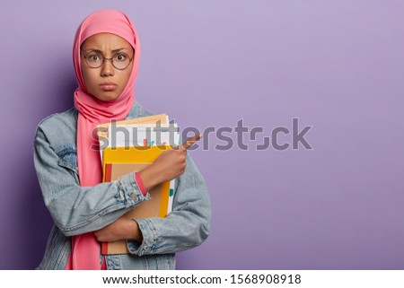 Teenage Muslim girl student poses with papers and textbooks, points aside on free space, wears round optical glasses and pink hijab, has puzzled face expression, isolated on violet background