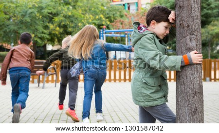 Teenage playing hide-and-go-seek in the playground