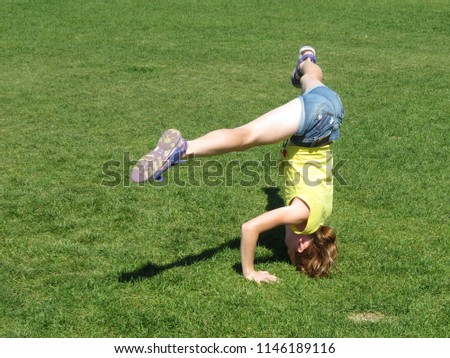 Stock Photo Teenage redhead girl in denim shorts performs a headstand with stretching. Yoga outdoors, fitness training, acrobatics on the green grass in summer meadow. Healthy lifestyle concept