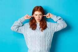 Teenage redhead girl unwilling to listen, shut ears and frowning angry, staring at camera offended, sulking against blue background