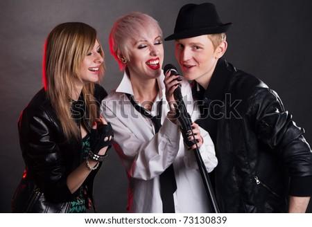 Teenage rock band against black background