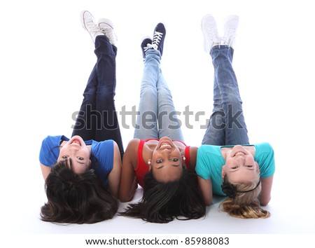 Teenage school student best friends lying on the floor looking backwards together made up of mixed race african american, oriental Japanese and caucasian all with happy smiles having a laugh.