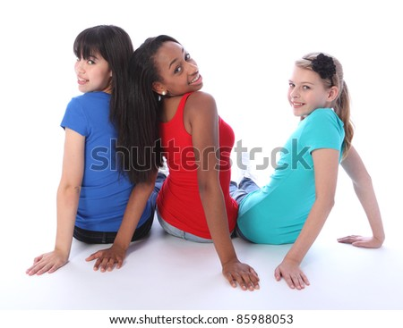 Teenage school student best friends sitting on the floor looking backwards together made up of mixed race african american, oriental Japanese and caucasian all with happy smiles having a laugh.