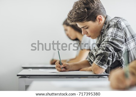Teenage schoolboy sitting at classroom and doing exam with his classmates.