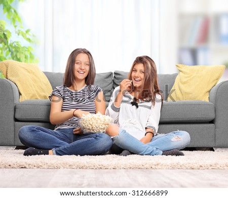 Teenage sisters eating popcorn and watching TV seated on the floor in front of a gray sofa at home