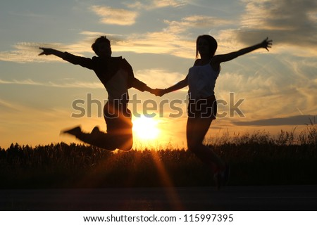 teenage sisters holding hands, doing exercises at sunset