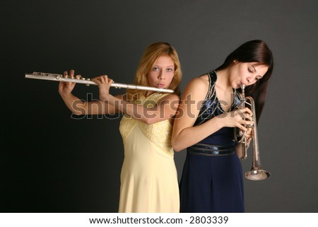 Teenage sisters with flute and trumpet wearing prom dresses against dark background