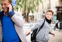 Teenage street thief stealing wallet from pocket of adult man absorbed in phone talk outdoors