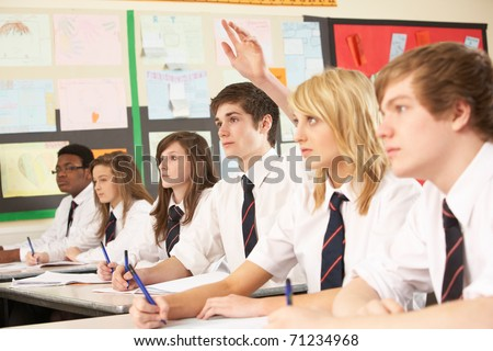 Teenage Student Answering Question Studying In Classroom