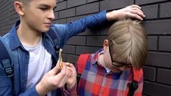 Teenage student extorting pocket money from classmate, school bullying, closeup