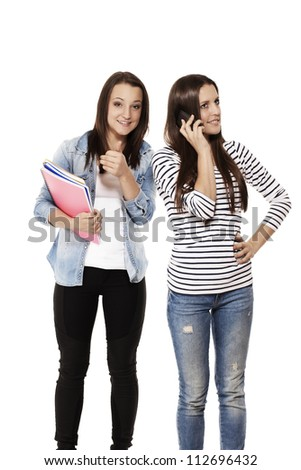 teenage student showing thumb up while her friend is on the phone on white background